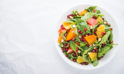 Fresh salad with fruits and greens on white background top view with space for text. Healthy food.