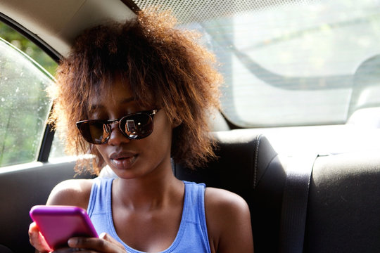 Young woman sitting n backseat of car looking at cell phone