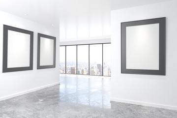 Blank picture frames on white walls in empty office with concret