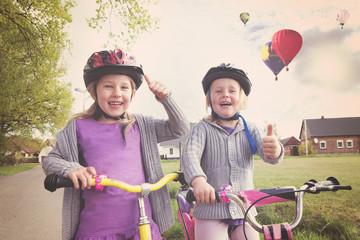 Portrait von Kindern auf Fahrrädern mit Daumen hoch