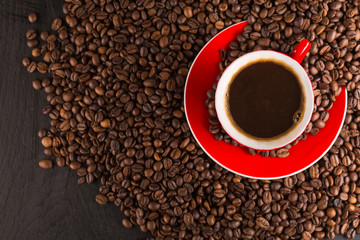 A red cup of coffee bean on the coffee beans background. Top view