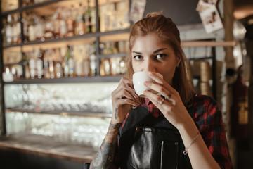 Break in work. Barista drinks coffee.