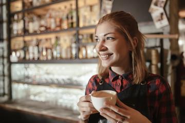 Break in work. Smiling woman barista drinks coffee.