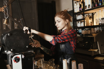 Female bartender pouring beer from faucet at bar