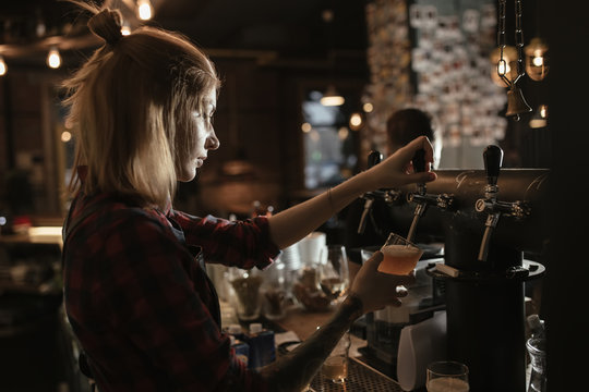 Female bartender pouring beer from tap at bar