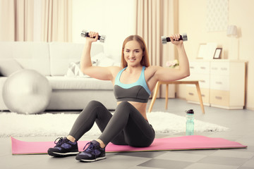 Young sportswoman doing exercises with dumbbells on a mat at home