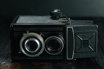 The old film camera on the old wooden table.