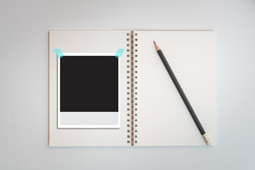 Polaroid photo frames on notebook and pencil