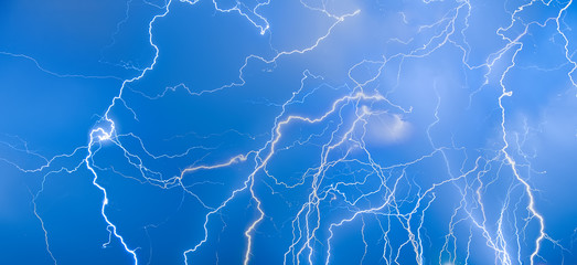 Flashes of lightning on a blue sky. Background