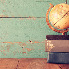 top view photo of vintage globe and stack of books on wooden desk. vintage filtered image