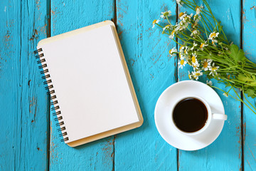 top view image of daisy flowers, blank notebook next to cup of coffee on blue wooden table.