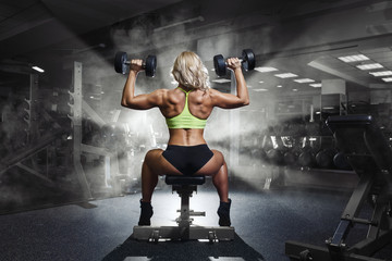 Professional sport fitness woman with weight disk in gym