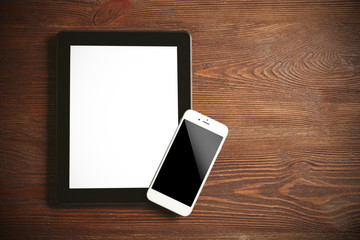 Modern mobile phone and tablet on wooden background