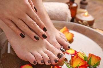 Manicured female feet and hand in spa wooden bowl with flowers and water closeup