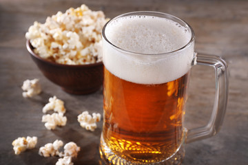 Glass mug of light beer with popcorn on wooden table, close up