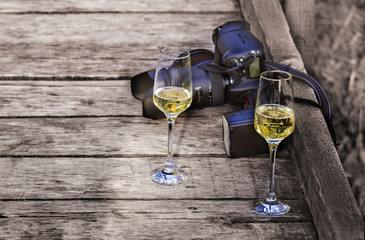 Two glasses of champagne and a photo camera