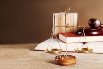Justice scales with wooden gavel and books on brown background