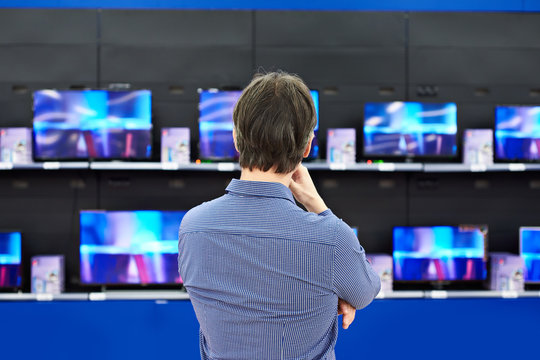 Man looks at LCD TVs in store