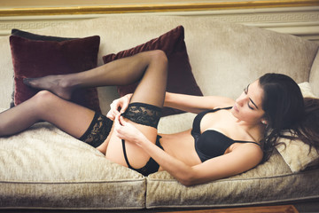 Sexy young woman in lingerie posing on a elegant couch