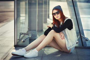 Outdoor lifestyle fashion portrait of pretty young sitting girl, wearing in hipster swag grunge style urban background. Red hair. Retro vintage toned image, film simulation.