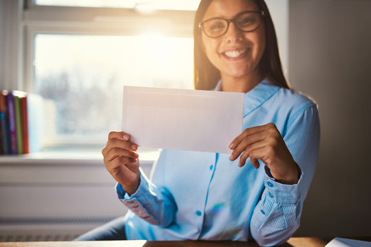 Woman sitting at desk with blank envelope
