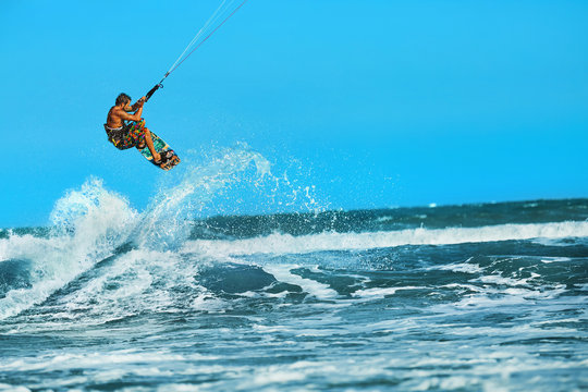 Recreational Water Sports Action. Healthy Man ( Surfer ) Kiteboarding ( Kite Surfing ) On Waves In Sea, Ocean. Extreme Sport. Summer Fun, Vacation. Active Lifestyle. Leisure Sporting Activity. Hobby