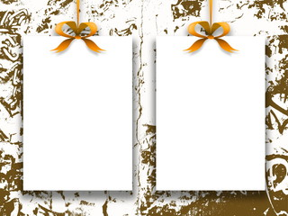 Close-up of two hanged paper sheets with golden ribbons on brown ink splotchy background