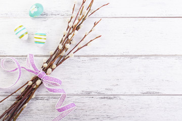 Colorful Easter eggs with willow branches and lila ribbon and copy space on a wooden background, top view..