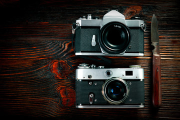 The old film cameras and the rusty german knife on the old wooden table.