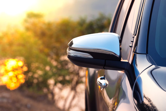 Black car side mirror with sun light effect. Travel and adventure concept.