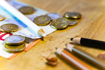 A white pencil surrounded by money is facing poor black and brown pencils in this racism and money inequality pencil concept.