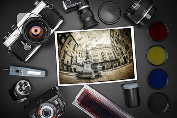 Analog SLR camera equipment around an old printed photo of a city square
