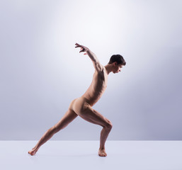 Athletic ballet dancer performing in a studio