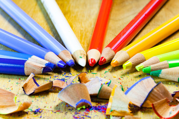 Colorful close up set of pencils and pencil shavings on a wooden table.