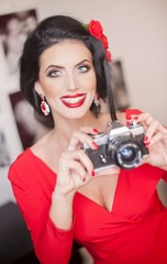 Beautiful young woman with creative make-up and hair style taking photos with a camera. Fashionable attractive brunette with Spanish look holding a camera. Lady in red with flower in hair, smiling