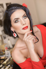 Beautiful young woman with creative make-up and hair style posing. Fashionable attractive brunette with Spanish look, indoors shot. Portrait of lady in red with flower in hair and gorgeous eyes