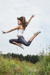 beauty girl jumping on green grass