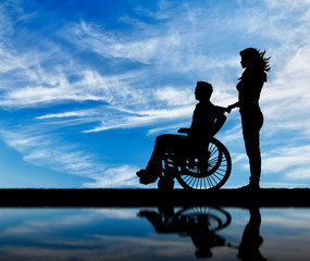 Silhouette of disabled person with a guardian