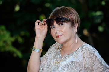 older Woman holding sunglasses