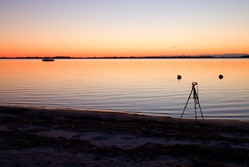 Silhouette of tall nature photographer at tripod taking picture on beach at sunset