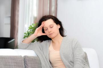 Frau mit Kopfschmerzen zu Hause