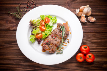 Beef steak with vegetables and seasoning on wooden background