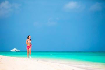 Fit female athlete girl runner running on beach