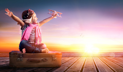 Fotobehang - Dream journey - Little Girl On Vintage Suitcase At Sunset