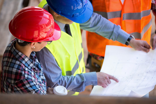 site manager  looking blueprint with architects
