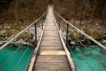 wooden bridge over turquoise soca river in slovenia