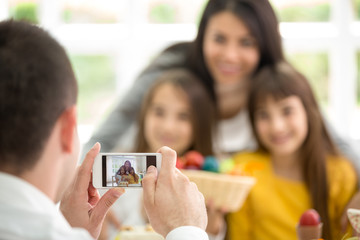 Father photographing family through smartphone at home