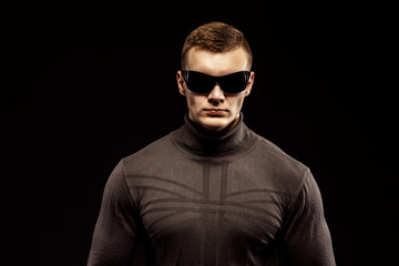 Combat muscled action hero man wearing shirt with pants and sunglasses. Studio shot. Robocop Style