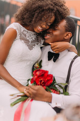 African wedding couple lovingly hugging with bouquet of red flowes