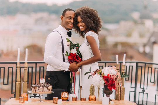Goregous black wedding couple happily smiling and holding hands